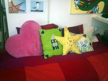 bed covered with pillows made by my daughter